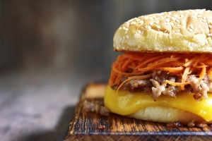 Homemade cheeseburger with fried minced meat and spicy carrot salad on a cutting board on rustic wooden background.Copy space.